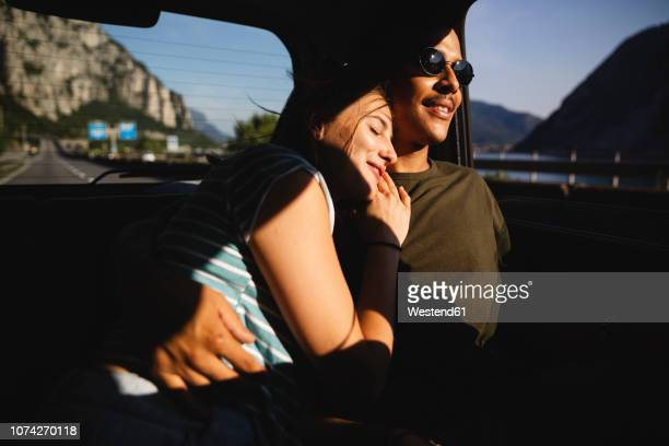 smiling affectionate young couple sitting on backseat in a car - chum stock-fotos und bilder
