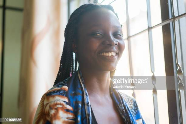 smiling african american black woman indoors on window - 30 34 years stock pictures, royalty-free photos & images