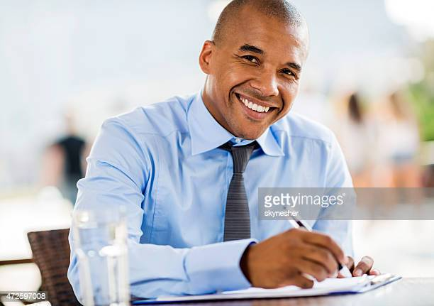 Smiling African American businessman doing paperwork in a cafe.