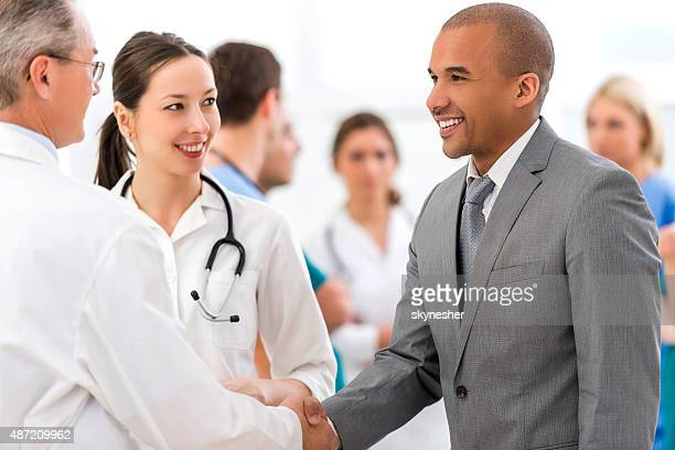 Smiling African American businessman shaking hands with doctor.