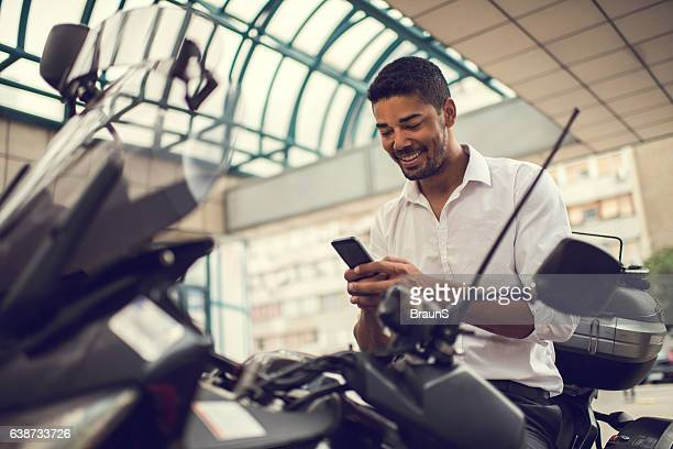 Smiling African American businessman using cell phone on motorcycle.