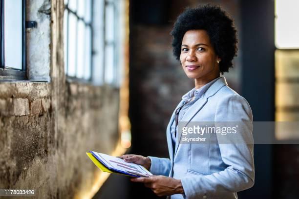 mulher de negócios de sorriso do americano africano com o documento no escritório. - diretora executiva de empresa - fotografias e filmes do acervo