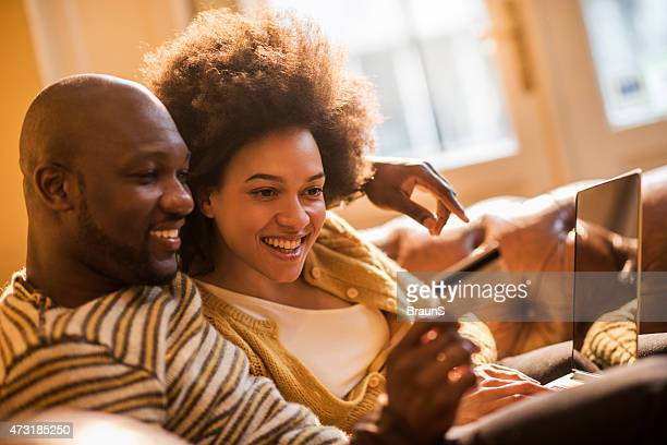 Smiling African American couple online shopping at home.