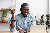 Smiling African American employee in headphones using laptop