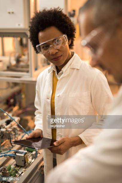 Smiling African American engineer cooperating with her colleague in laboratory.