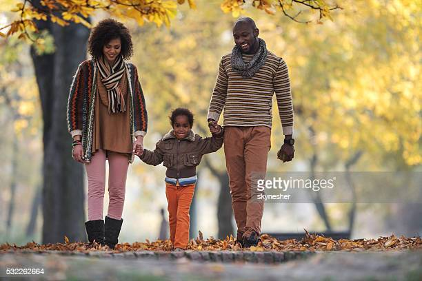 Smiling African American family taking a walk in autumn park.