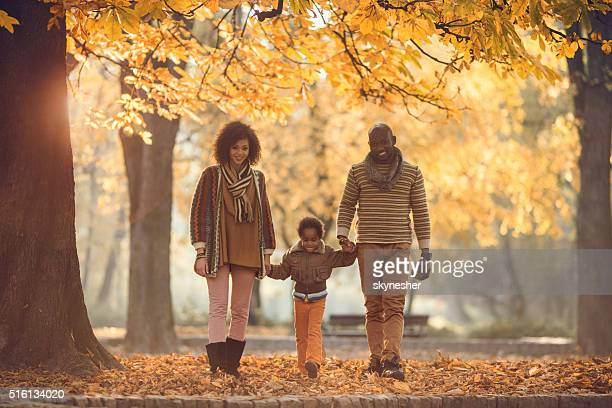 Smiling African American family walking in autumn park together.