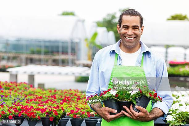 Smiling African American garden center employee with flowers