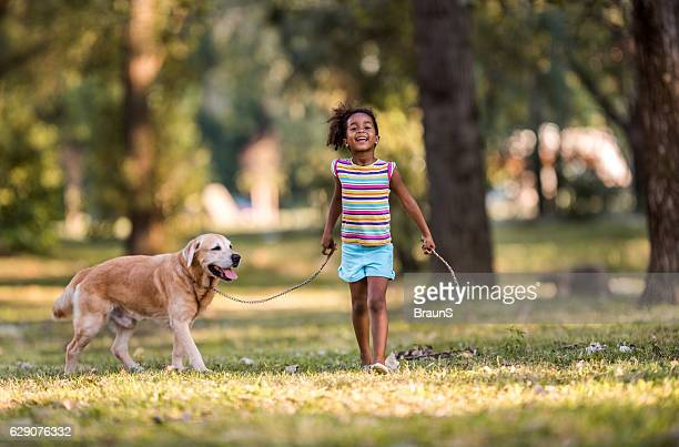 Smiling African American girl walking her dog on a leash.