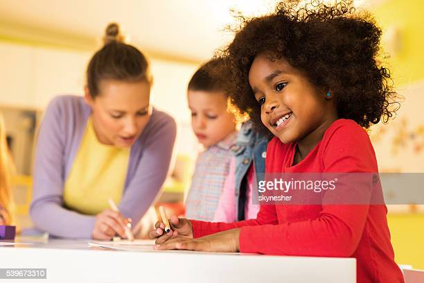 Smiling African American little girl sketching at kindergarten.