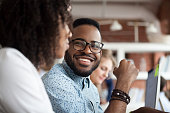 Smiling African American male employee look at colleague chatting