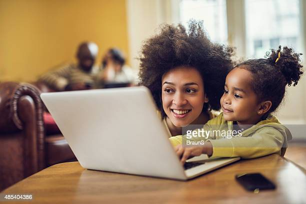 Smiling African American mother and daughter using laptop at home.