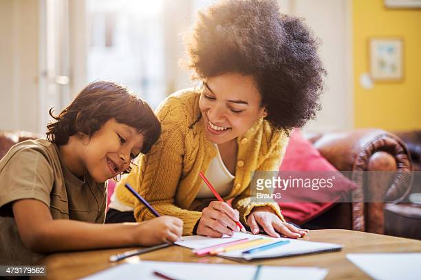 smiling african american mother and son coloring together. - colouring stock pictures, royalty-free photos & images