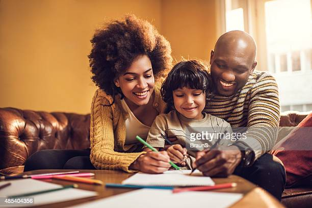 Smiling African American parents coloring with their little boy.