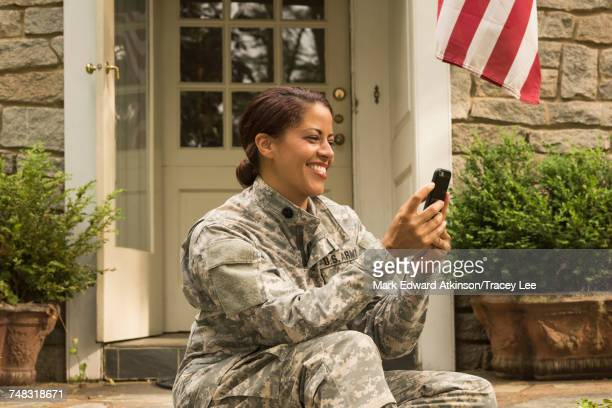 Smiling African American soldier sitting on front stoop texting on cell phone