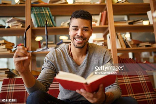 Smiling African American student enjoying book reading in library.