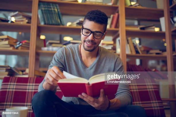 sorrindo o estudante americano africano, apreciando a leitura de livros na biblioteca - romance - fotografias e filmes do acervo