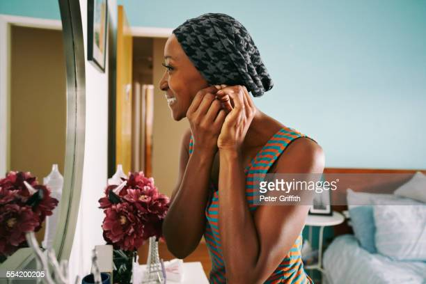 smiling african american woman attaching earring - putting stock pictures, royalty-free photos & images