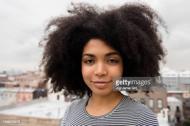 smiling african american woman posing on rooftop - afro amerikaanse etniciteit stockfoto's en -beelden