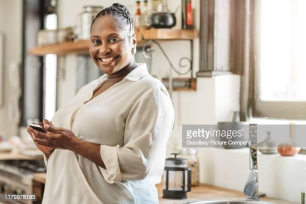 femme d'afro-américain de sourire affichant un message texte à la maison - chubby photos et images de collection