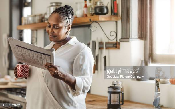 smiling african american woman reading the newspaper in the morning - reading stock pictures, royalty-free photos & images
