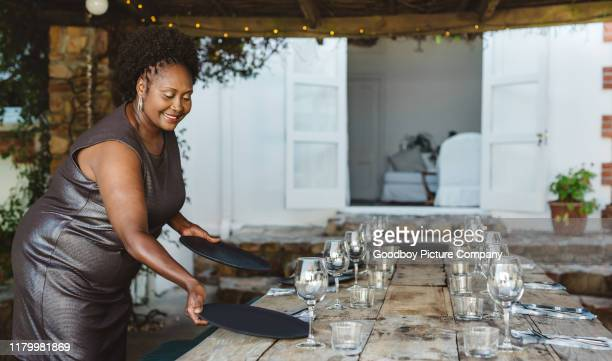 smiling african american woman setting her table for a party - party host stock pictures, royalty-free photos & images