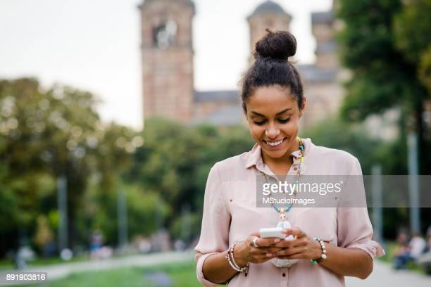 Smiling African American woman text messiging
