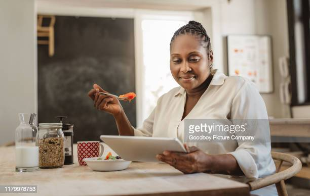 smiling african american woman using a tablet and eating breakfast - large build stock pictures, royalty-free photos & images