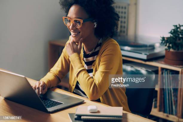 smiling african american woman wearing glasses and wireless earphones makes a video call on her laptop computer at her home office - african american ethnicity stock pictures, royalty-free photos & images