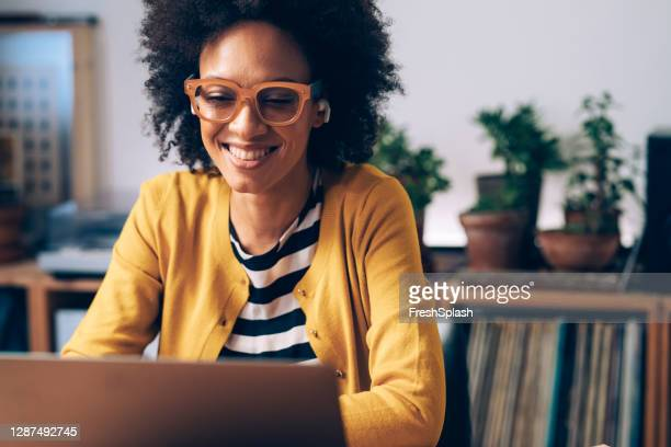 mulher afro-americana sorridente usando óculos e fones de ouvido sem fio faz uma chamada de vídeo em seu computador portátil em seu home office - attending - fotografias e filmes do acervo