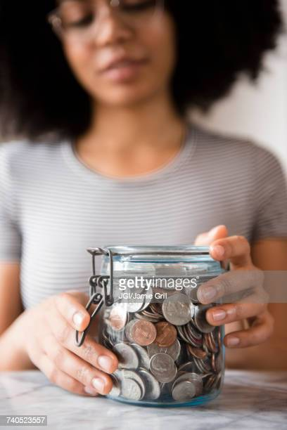 Smiling African American woman with jar full of coins