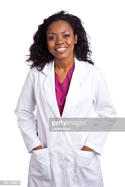 Smiling African ethnicity female wearing lapcoat hands in pockets