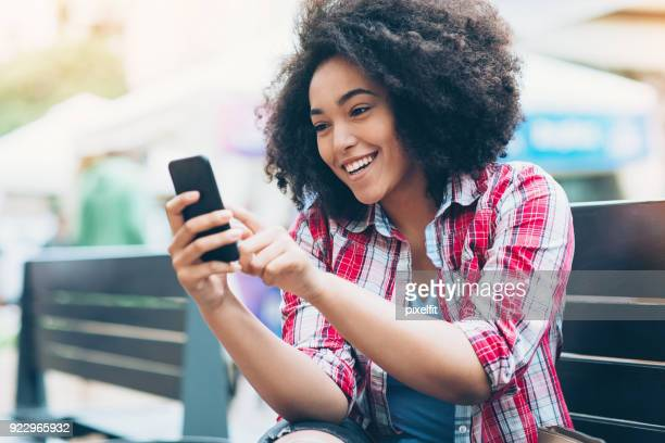 Smiling African ethnicity girl texting outdoors