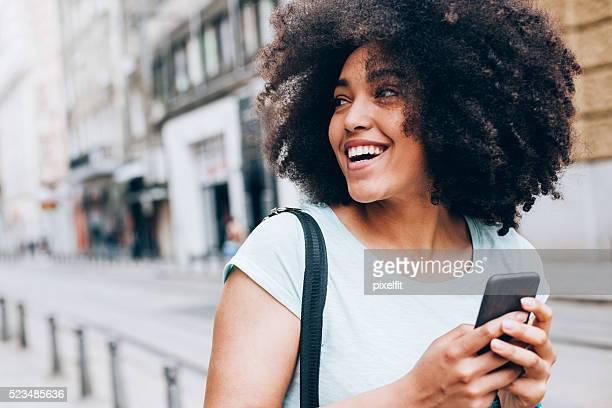 Lächelnd Afrikanischer Abstammung Mädchen mit Smartphone