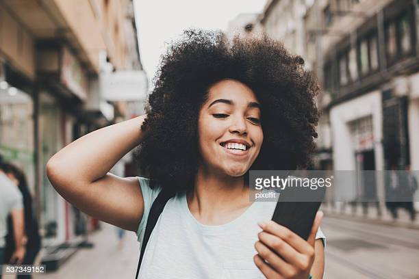 smiling african ethnicity girl with smart phone - creole ethnicity stock pictures, royalty-free photos & images