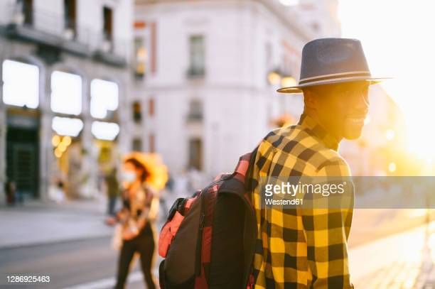 smiling african man with backpack walkingin city during sunset - strap stock pictures, royalty-free photos & images