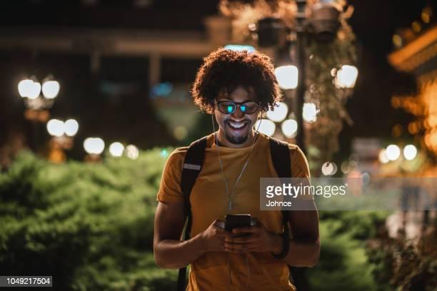lächelnde afrikanische student sms außerhalb - instant messaging stock-fotos und bilder