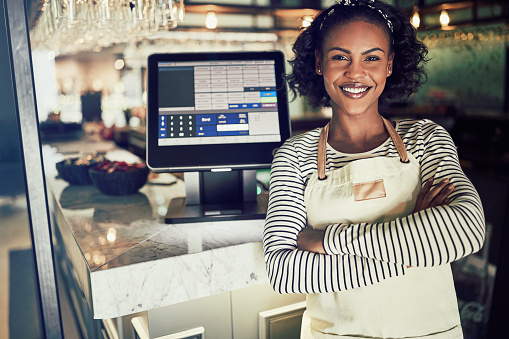 Smiling African waitress standing at the counter of a restaurant 946157268