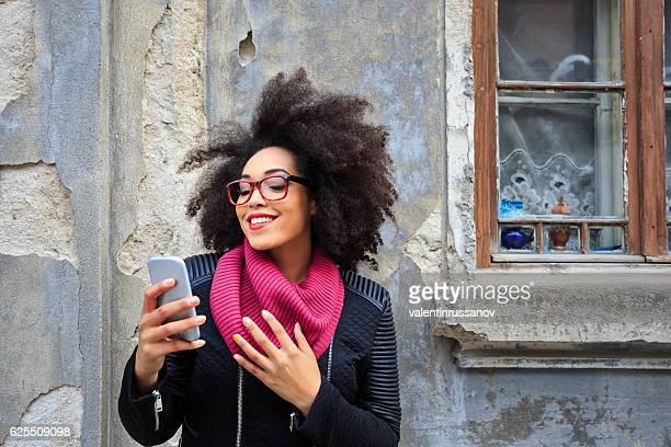 smiling african woman making selfie in front of vintage building - chaqueta rosa fotografías e imágenes de stock