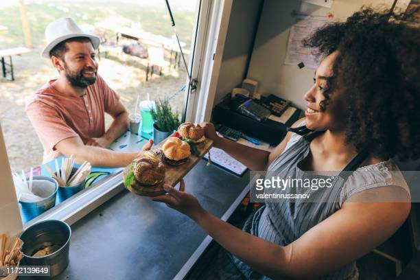smiling african woman selling burgers in food truck - food truck stock pictures, royalty-free photos & images