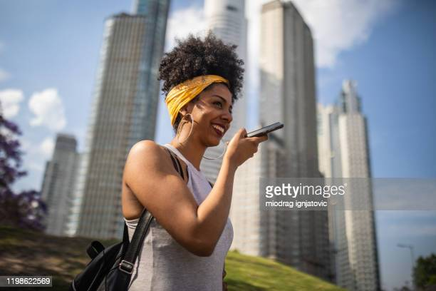 smiling  african-american lady sending voice message outdoor - speech recognition stock pictures, royalty-free photos & images