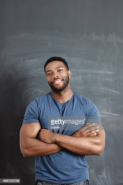 smiling afro american man against blackboard - most handsome black men stock photos and pictures