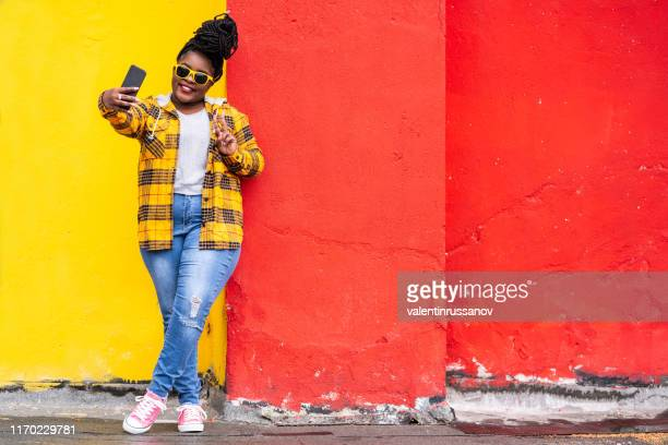 smiling afro woman on colorful background taking selfie - plus size model stock pictures, royalty-free photos & images