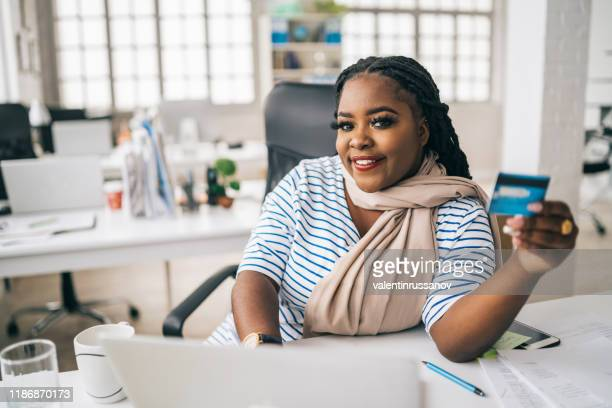 smiling afro woman using credit card and laptop at home - chubby credit stock pictures, royalty-free photos & images