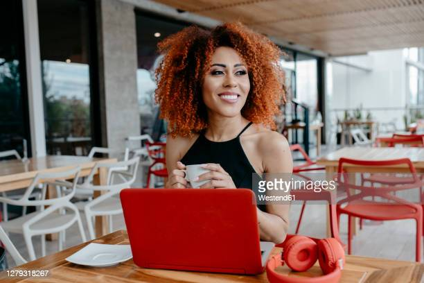 smiling afro woman with laptop on table holding coffee cup while sitting at sidewalk cafe - コイリーヘア ストックフォトと画像