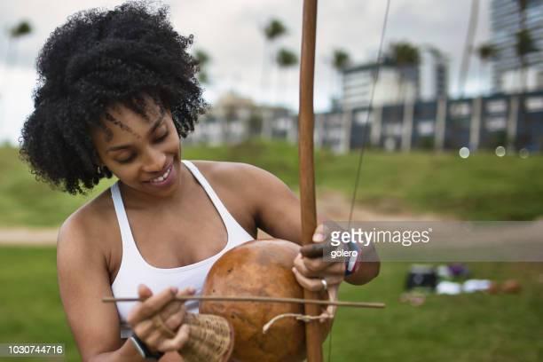 smiling  afro-brazilan woman playing berimbau at beach - capoeira imagens e fotografias de stock