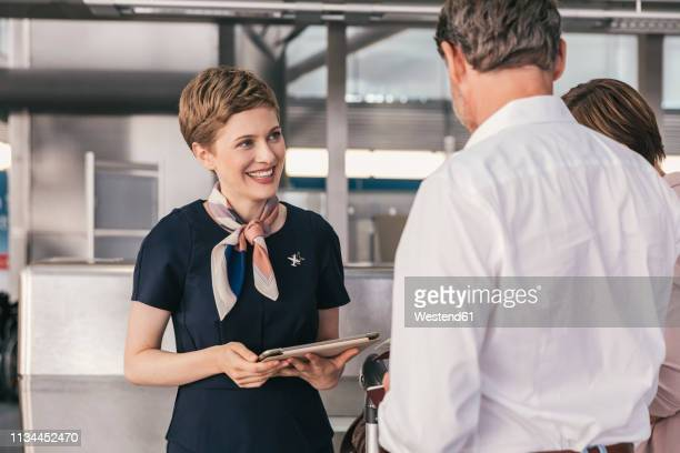 smiling airline employee talking to couple at the airport - crew stock pictures, royalty-free photos & images