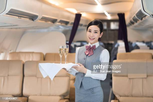Smiling airline stewardess serving champagne on airplane