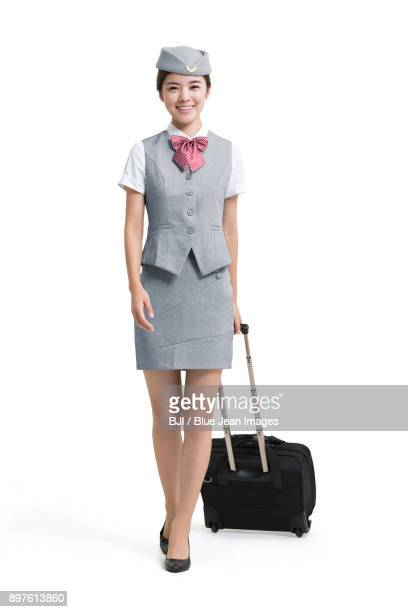 Smiling airline stewardess with wheeled luggage