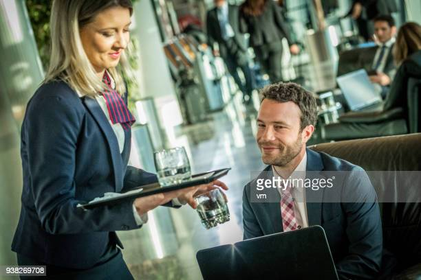 Smiling airport waitress serving water to smiling businessman